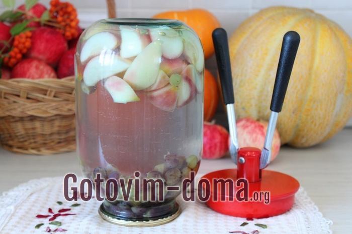 Банка с компотом из яблок и винограда вверх дном