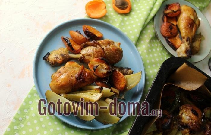 Куриные ножки с абрикосами и картофелем на тарелке