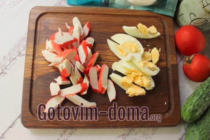 Крабовые палочки и яйца порезаны для салата