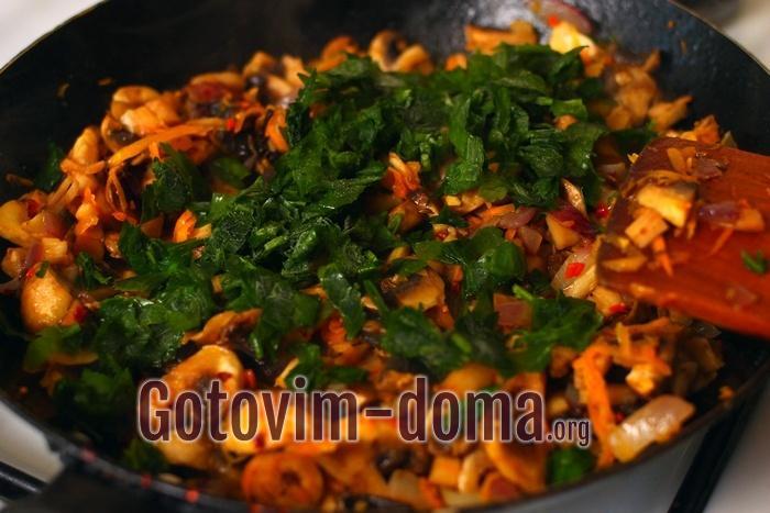 Грибы, овощи и зелень тушатся для грибного пирога
