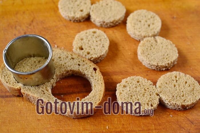 Из черного хлеба вырезаем кружочки для канапе с сельдью.