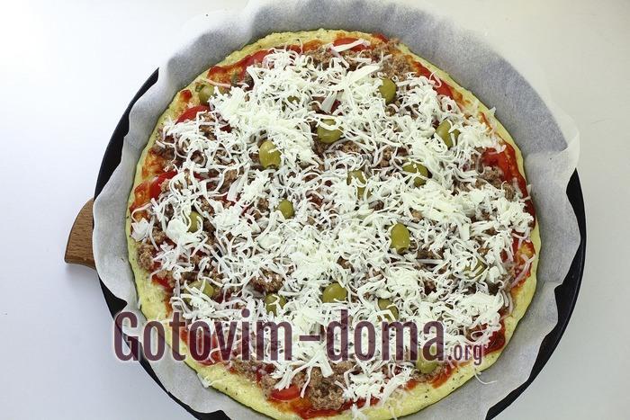 Верх пиццы посыпан моцареллой.