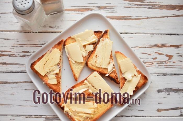 Обжаренные гренки намазаны сыром.