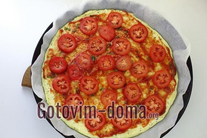Помидоры колечками выложены на пиццу.