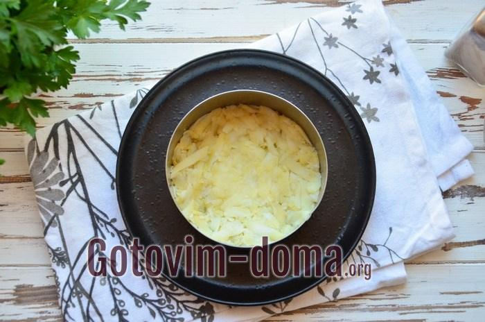 В кулинарное кольцо выложен тертый картофель.