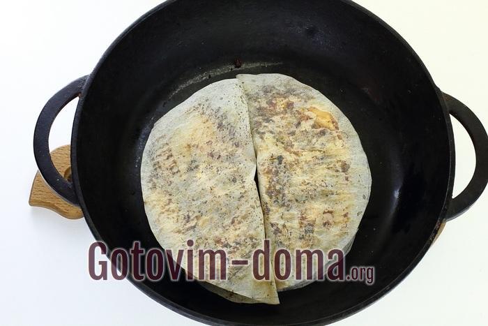 Куриное филе в пергаменте обжаривается на сковороде.